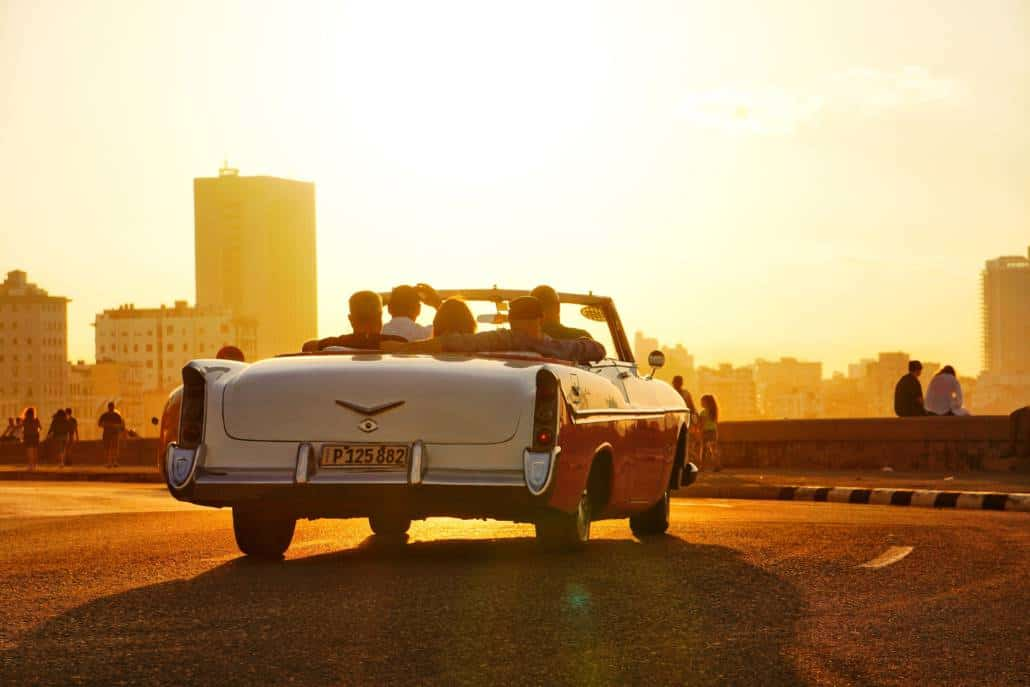 a car riding into the sunset in havana cuba on malecon